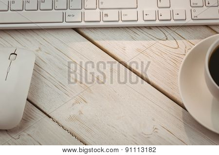White keyboard and cup of coffee on a desk