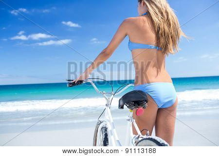 Pretty blonde woman going on a bike ride at the beach