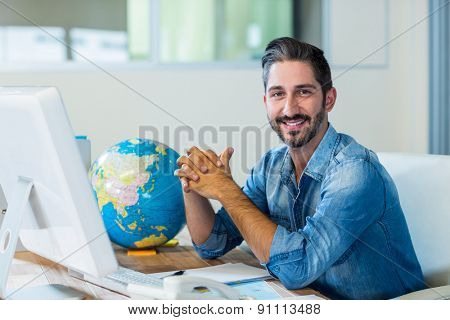 Smiling businessman sitting at his desk in the office