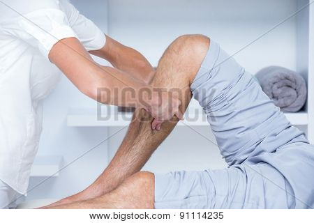 Physiotherapist doing calf massage to her patient in medical office