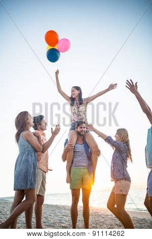 Happy friends dancing on the sand with balloon at the beach