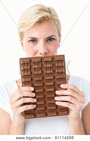 Attractive woman holding big bar of chocolate on white background