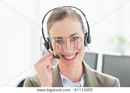 Smiling businesswoman with headset looking at camera in office