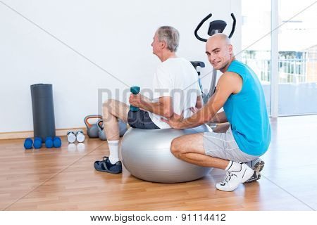 old man having back massage on exercise ball in medical office