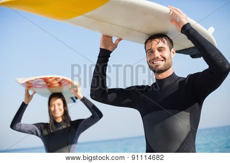 happy couple in wetsuits with surfboard on a sunny day at the beach