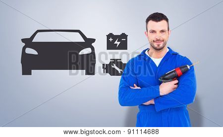 Confident handyman holding power drill against grey vignette