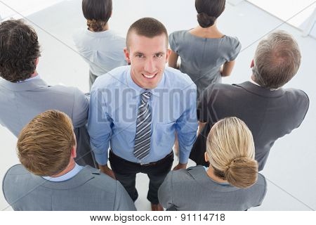 Businessman looking at camera and business team standing back to camera in the office