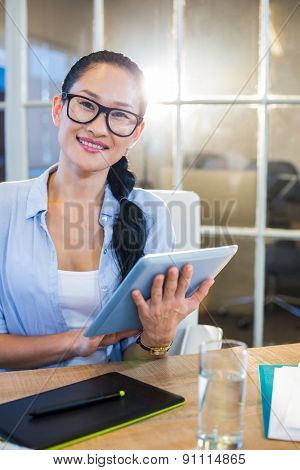 Smiling businesswoman sitting at her desk and working with tablet in the office