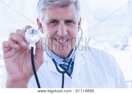 Happy doctor smiling at camera and showing his stethoscope in medical office