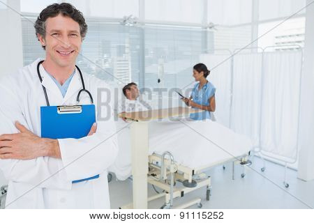 Smiling doctor holding patients file in hospital room