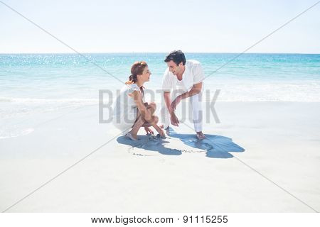 Happy couple drawing heart shape in the sand at the beach