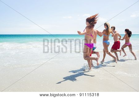 Happy friends running in the water together at the beach
