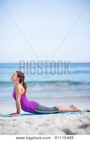 Brunette doing yoga on exercise mat at the beach