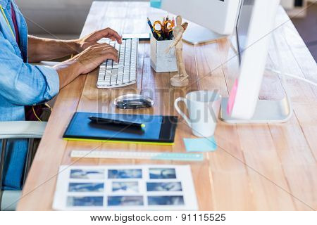 Businessman typing on keyboard at desk in the office