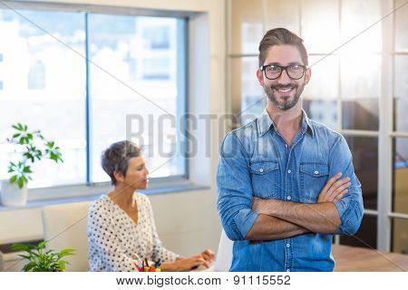Smiling man standing arms crossed with his partner behind in the office