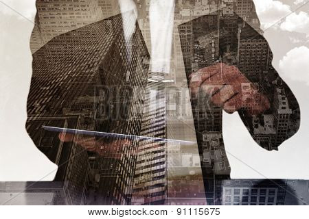 Businessman looking at his tablet through magnifying glass against low angle view of skyscrapers