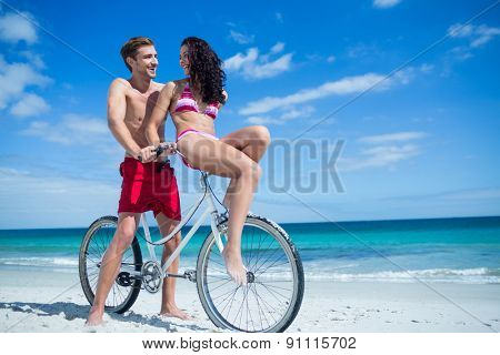 Happy couple going on a bike ride at the beach