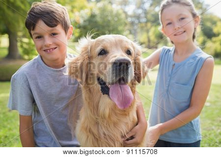 Smiling sibling with their dog in the park on a sunny day