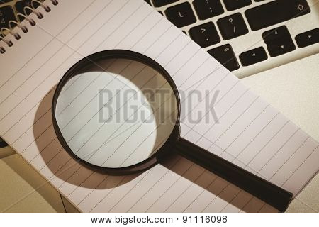Magnifying glass and notepad on laptop on a desk