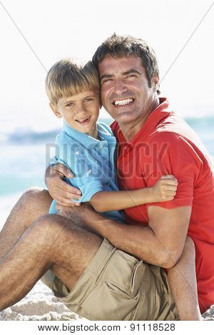Father And Son Sitting On Beach Together