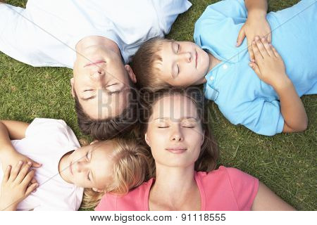 Overhead View Of Family Resting On Grass