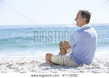 Senior Man On Holiday Sitting On Sandy Beach