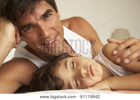 Father Comforting Sleeping Son In Bed
