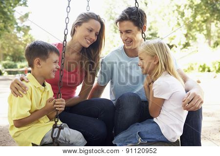 Family Sitting On Swing In Playground