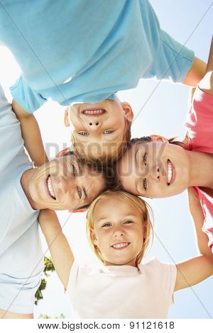 Close Up Of Family Group Looking Down Into Camera In Park