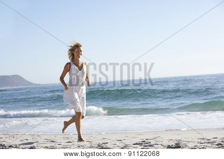 Casually Dressed Young Woman Running Along Beach