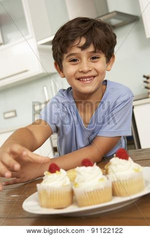Young Boy Eating Cakes In Kitchen