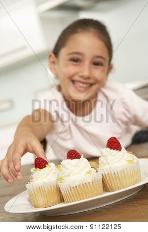 Young Girl Eating Cakes In Kitchen