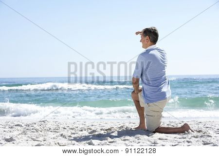 Senior Man On Holiday Kneeling On Sandy Beach