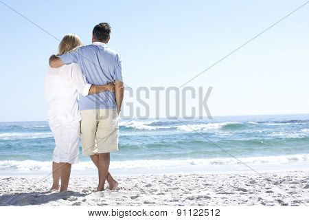 Senior Couple On Holiday Walking Along Sandy Beach Looking Out To Sea