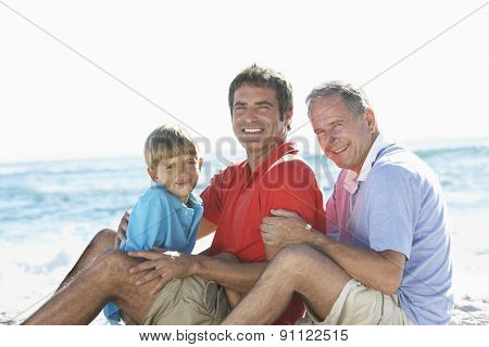 Grandfather With Grandson And Father Embracing On Beach Holiday