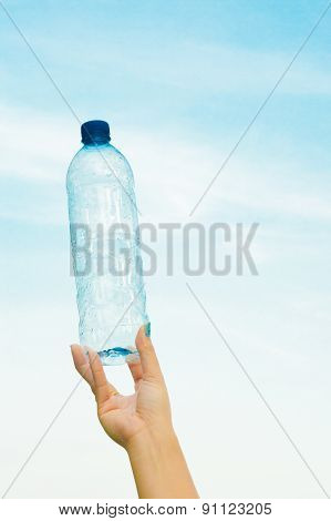 Woman Hand Holding A Bottle Of Water In The Sky.