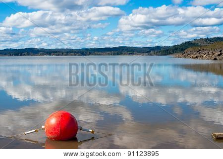 Red Buoy on a Clear Reflective Lake