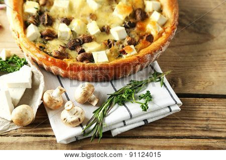 Cheese pie with mushrooms, herbs and sour creme, on wooden table background