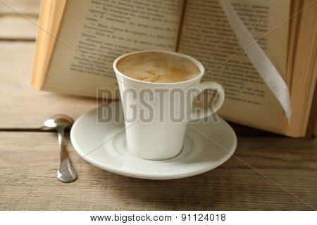 Still life with cup of coffee and book, on wooden table