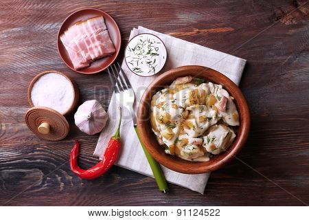 Fried dumplings with onion and bacon in frying pan, on wooden table background