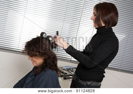 Hairstylist Combing  Client In Hairdressing Salon