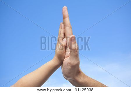 Father And Son In High Five Gesture On A Blue Sky With Some Clouds Background
