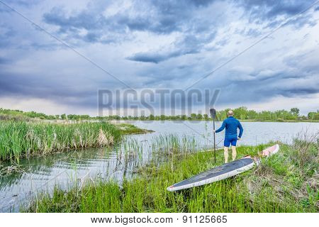senior male with stand up paddleboard on lake shore watching stormy clouds