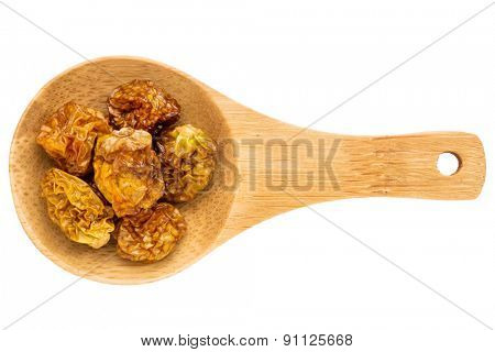 dried goldenberries on a small wooden spoon isolated on white with a clipping path