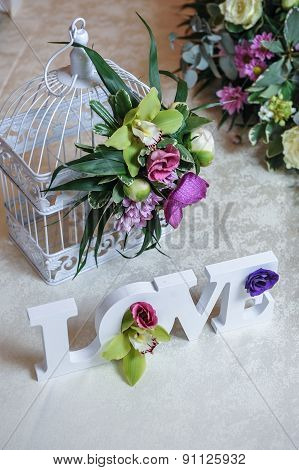 Wedding decor, LOVE letters and flowers on table. Fresh flowers and LOVE decoration on festive table