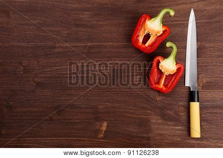 Halves of pepper with knife on wooden background