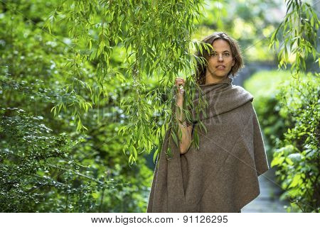 Young beautiful woman in poncho among the green foliage in the garden.