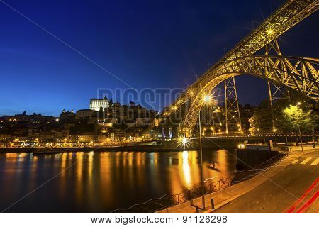 View of the historic city of Porto, Portugal with the Dom Luiz I bridge at night time.