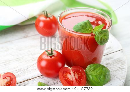Glass of fresh tomato juice on wooden table, closeup