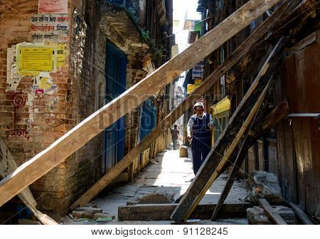 KATHMANDU, NEPAL - MAY 14, 2015: Man walks down an alley where wood beams support damaged buildings after two major earthquakes hit Nepal in the past weeks.